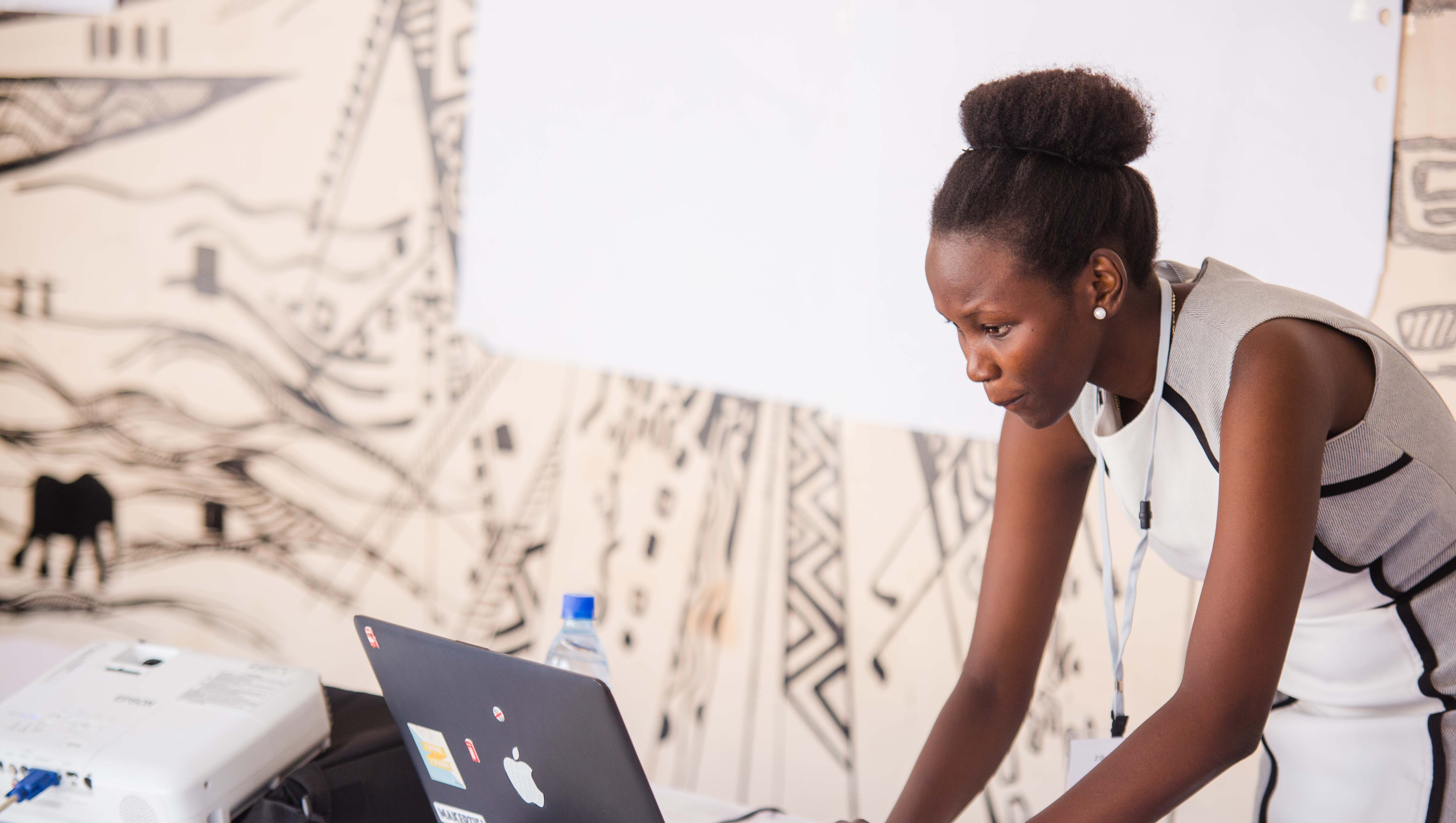Black woman in a white dress leans over her laptop