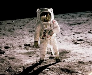 A person in a space suit standing on the moon