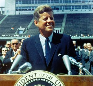 President John F Kennedy standing on a podum looking off and smiling to the right