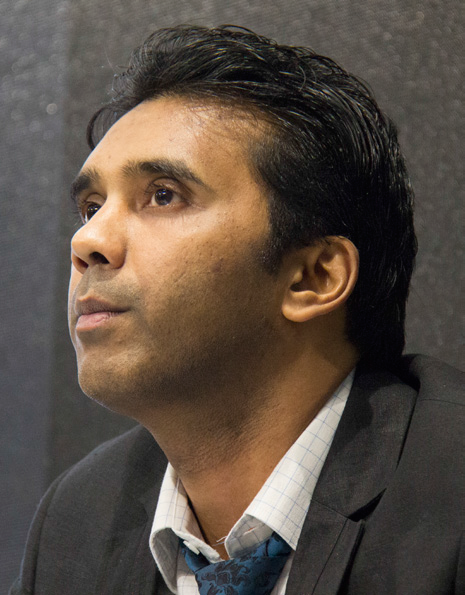An Indian man wearing a dark suit and a white shirt, looks off to the left of the camera