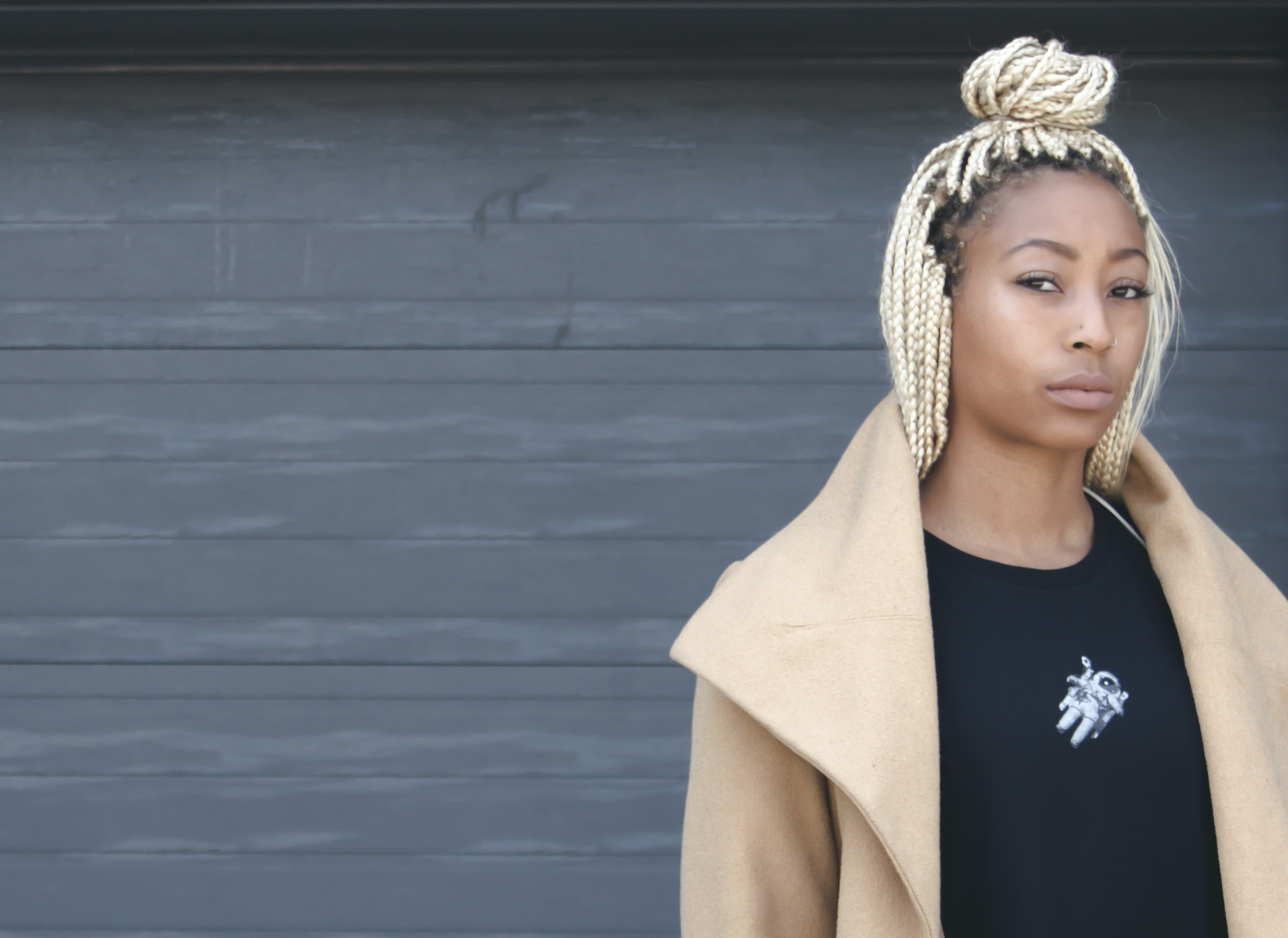 Black woman with white braids, wearing a black t shirt and camel jacket