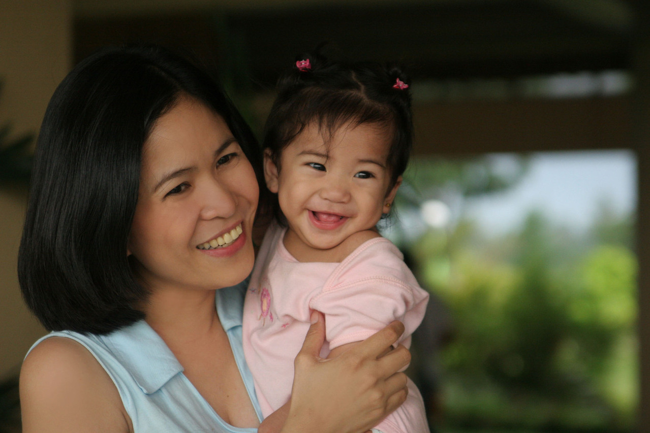 Asian woman holding a child, dressed in pink