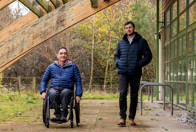 Two men dressed in outdoor clothes in a woodland area, the man on the left is in a wheelchair
