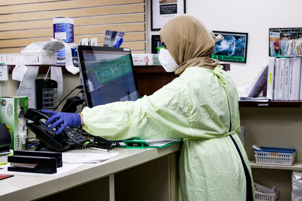 Woman in green protective apron and a brown headscarf and mask working in a pharmacy